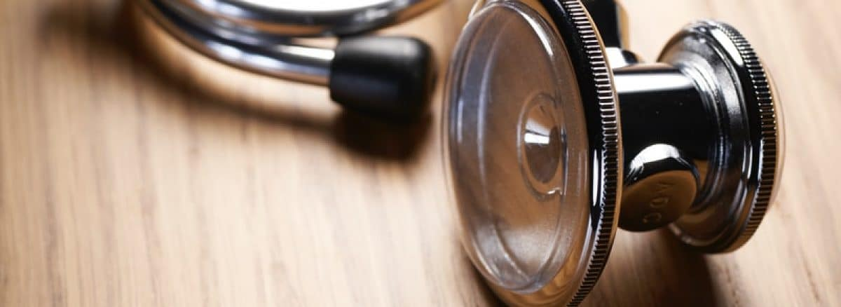 shallow focus photo of blue and gray stethoscope on brown wooden table